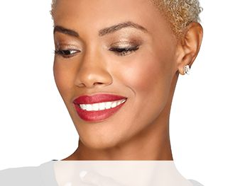 A smiling woman is wearing a Mary Kay® makeup look that features golden eye shadow shades and a berry blush and lipstick for a stunning, glowing look.