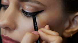 Eyeliner being applied to a model's lashline with the Mary Kay Eyebrow/Eyeliner Brush.
