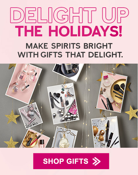 Mary Kay® products in cards on gray background with lights and stars
